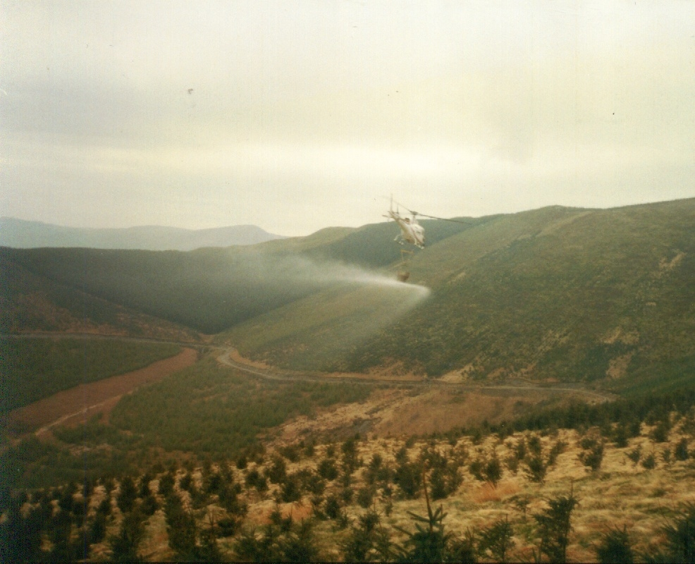 Aerial fertiliser spreading in progress (forestry and mountain pasture).
